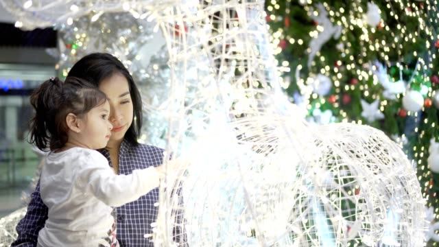 mother and daughter playing with light in festive christmas - gente serena video stock e b–roll