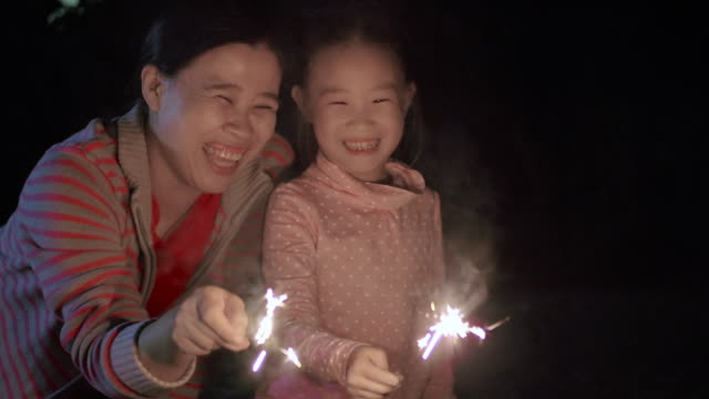 SLO MO Mother and daughter playing with sparklers family love emotion