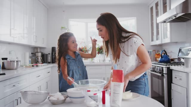 Mother and daughter preparing cake mix, tasting it and dabbing it on each otherÕs noses, close up