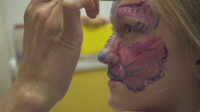 mother and daughter preparing for Halloween celebration and making painted scary face make-up to each other