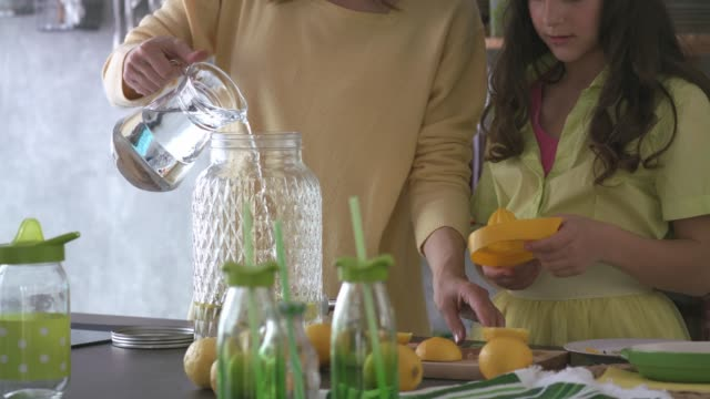 mother and daughter preparing tasty, refreshing lemonade together - gusto aspro video stock e b–roll
