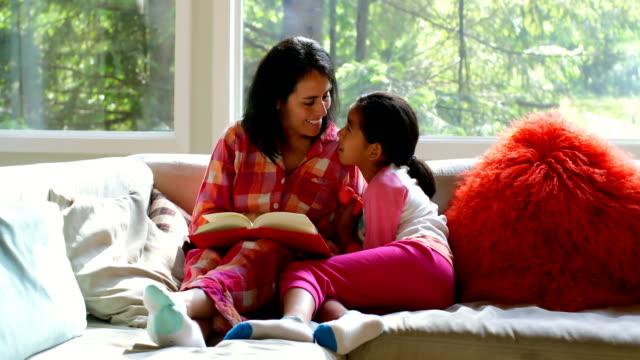 mor och dotter läsebok i vardagsrummet 4k - cosy pillows mother child bildbanksvideor och videomaterial från bakom kulisserna