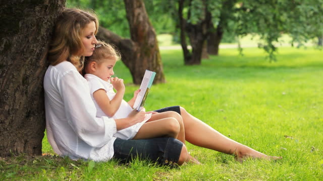 Mother and daughter reading book in park video