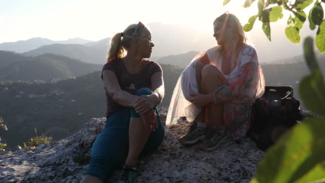 mother and daughter relax above forest and hills at sunrise - pantaloni capri video stock e b–roll