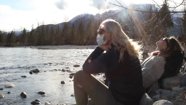 Mother and daughter relax beside moving mountain river