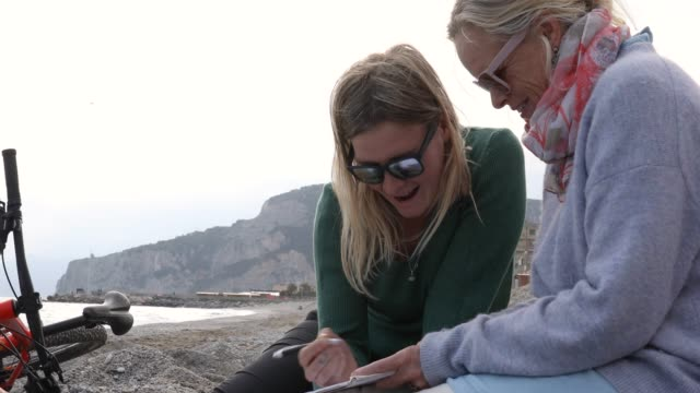 Mother and daughter relax on beach, with writing tablet