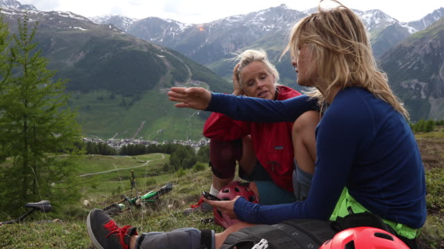 mother and daughter relax on bike ride, in meadow - livigno video stock e b–roll