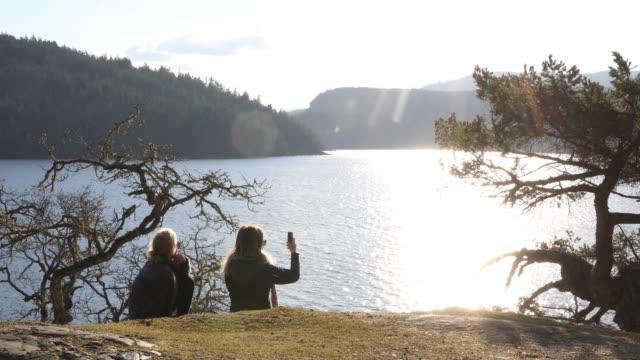 vídeos y material grabado en eventos de stock de madre e hija relajarse, tomar pic teléfono inteligente - memorial day weekend