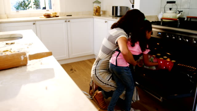 Mother and daughter removing tray of cookies from oven in kitchen video