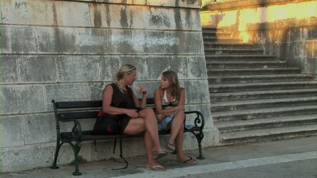 Mother and daughter resting on bench Mother and daughter resting on bench cross legged stock videos & royalty-free footage
