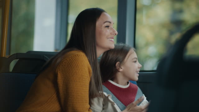 Mother and daughter riding on the bus together Mother and daughter riding on the bus together. They are looking thru window and mother explaining what they are seeing. effortless stock videos & royalty-free footage