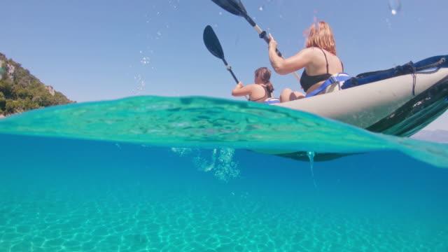 vídeos de stock, filmes e b-roll de ms-mãe e filha, remar caiaque no oceano azul turquesa ensolarado, peljesac, croácia - remo esporte aquático