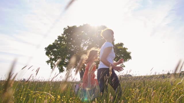 slo mo mother and daughter running in grass - kameraåkning på räls bildbanksvideor och videomaterial från bakom kulisserna