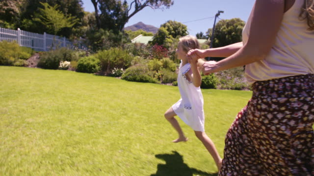 Mother and daughter running in their backyard video