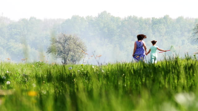 vidéos et rushes de mère et fille s'exécutant sur le champ de printemps - fête des mères