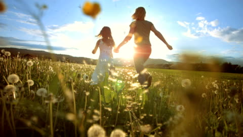 SUPER SLO MO Mother And Daughter Running To The Sun HD1080p: Super Slow Motion shot of a mother and her little daughter running in the meadow at sunset. Rear-view tracking shot. family stock videos & royalty-free footage