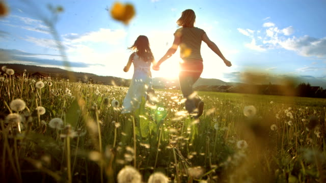 SUPER SLO MO Mother And Daughter Running To The Sun HD1080p: Super Slow Motion shot of a mother and her little daughter running in the meadow at sunset. Rear-view tracking shot. love emotion stock videos & royalty-free footage