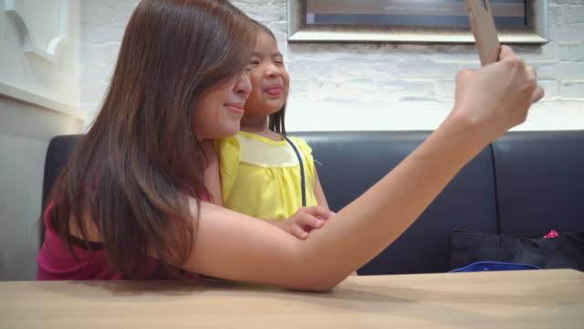 mor och dotter selfie - birthday celebration looking at phone children bildbanksvideor och videomaterial från bakom kulisserna