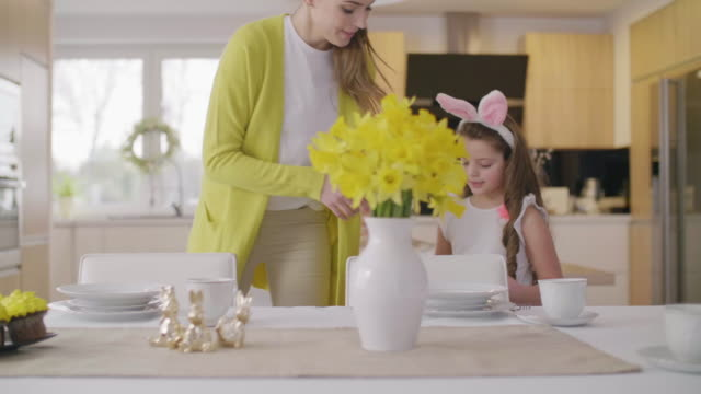 Mother and daughter setting table for easter brekfast