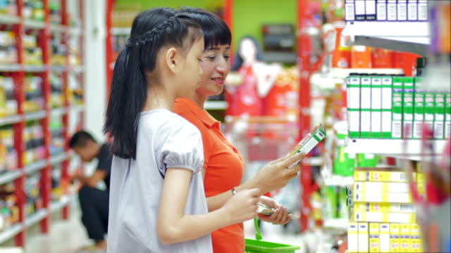Mother and daughter shopping in supermarket video