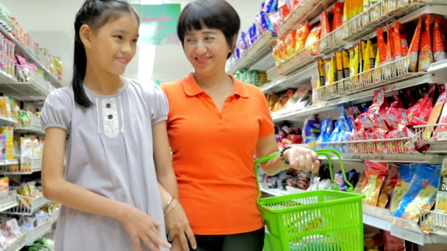 Mother and daughter shopping in supermarket,Slow motion video