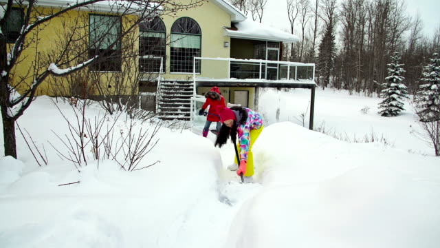 Mother and daughter shoveling snow off house deck and walkway video