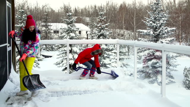 Mother and daughter shoveling snow off house deck video