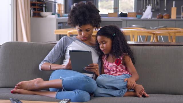 vídeos y material grabado en eventos de stock de madre e hija sentarse en el sofá en el salón con tableta digital - madre e hijos