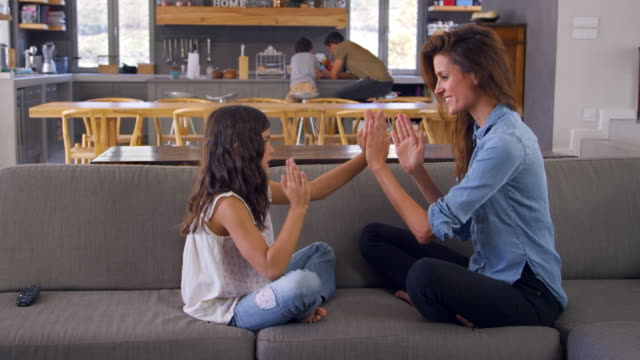 Mother And Daughter Sitting On Sofa Playing Clapping Game video