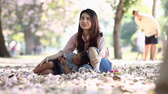 Mother and daughter sitting under a tree and enjoy the view with pink flowers fall, filling the table.