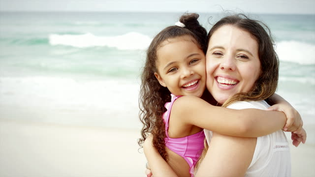Mother and daughter smile on a beach in Brazil video