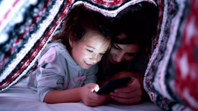 Mother and daughter surfing the net in bed video