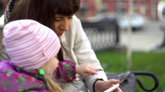Mother and daughter take sefi while sitting on a bench near a busy road. video