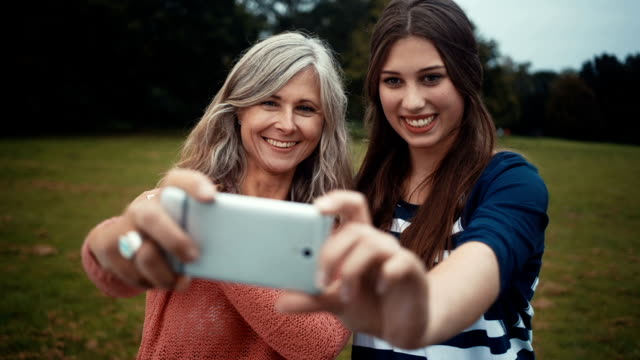 vídeos y material grabado en eventos de stock de madre e hija tomar selfie con smartphone - hija