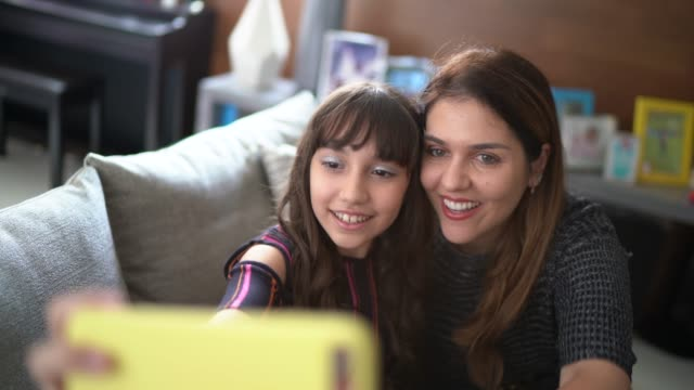 mother and daughter taking a selfie at home - video call with family video stock e b–roll