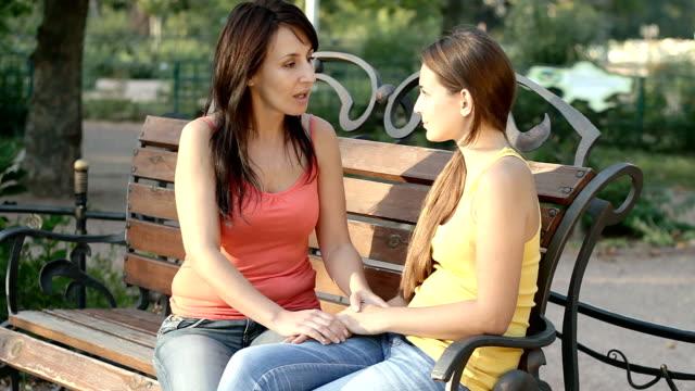 mother and daughter talking outdoors in summer park - parent talking to child bildbanksvideor och videomaterial från bakom kulisserna