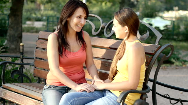 Mother and daughter talking outdoors in summer park video