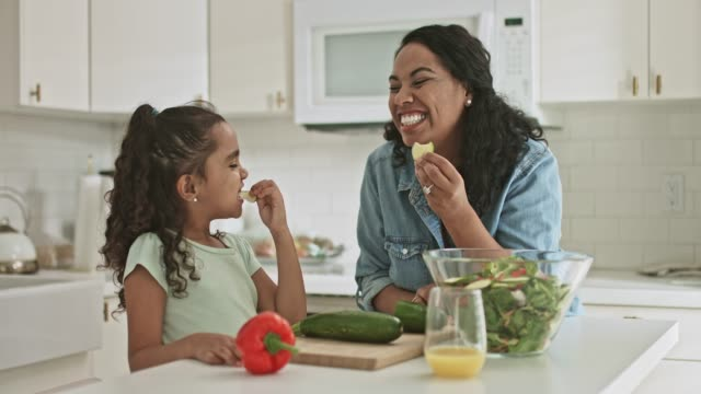 mor och dotter smakar lite zucchini mat medan du förbereder mat hemma - sallad bildbanksvideor och videomaterial från bakom kulisserna