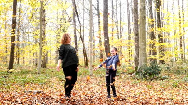母と娘。空気中の葉を投げる ビデオ