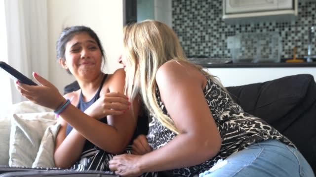 madre e figlia solleticano mentre sono sedute sul divano - fare il solletico video stock e b–roll