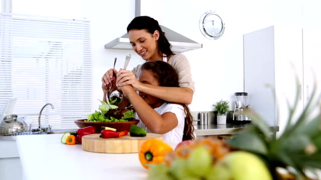 Mother and daughter tossing salad together video
