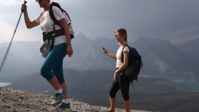 mother and daughter traverse mountain ridge crest - pantaloni capri video stock e b–roll