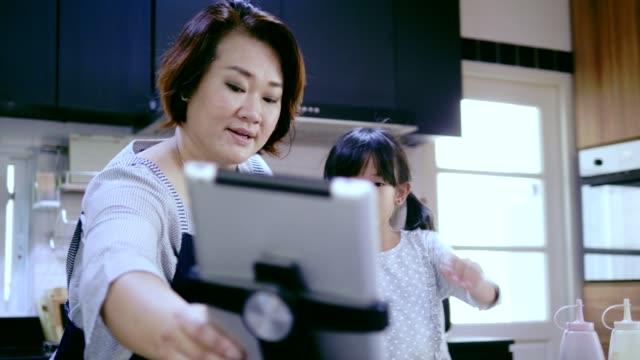 mor och dotter försöker baka mellanmål från lutande online - videor med baka bildbanksvideor och videomaterial från bakom kulisserna