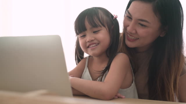 vídeos de stock e filmes b-roll de mother and daughter using a laptop together - girl study home laptop front