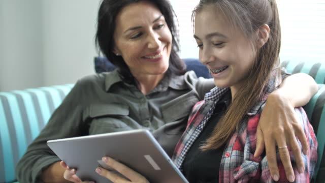 mor och dotter använder digitala tablett - digital reading child bildbanksvideor och videomaterial från bakom kulisserna