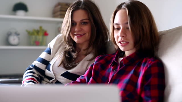 Mother and daughter using lap top at home video