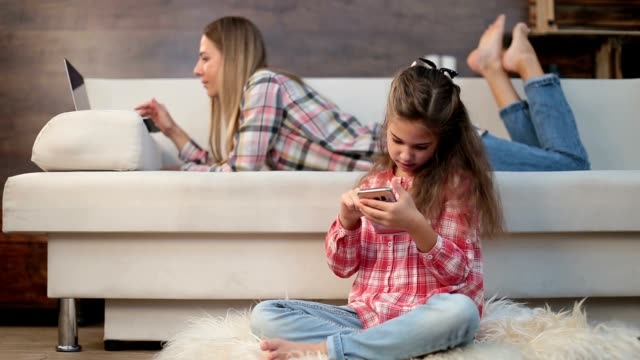 Mother and daughter using laptop and phone at home video