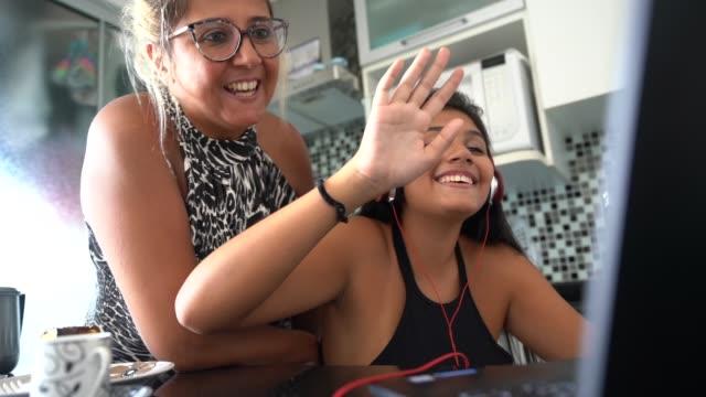 mor och dotter använder laptop medan du lyssnar på musik hemma - latino music bildbanksvideor och videomaterial från bakom kulisserna