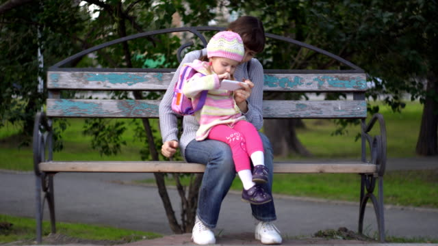 Mother and daughter using phone on outside a cool evening video