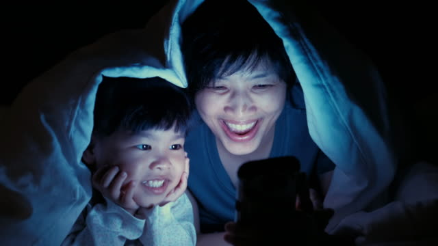 Mother and Daughter using smart phone under blanket video